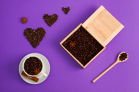 Cup of coffee seeds, cinnamon, anis coffee heart shapes, wooden box and spoon with coffee  on purple background. I love coffee, coffee lover concept. Horizontal orientation, close up. Фото со стока