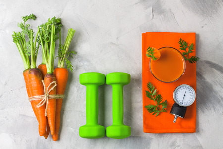 Bunch of fresh carrot tied with twine, green dumbbells glass of juice and manometer of pressure measuring device on grey concrete. Concept carrot for health, normalization of arterial pressure, sport.