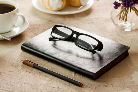 105bdf9ea Black leather notepad, black-rimmed spectacles, pen with brown cap, white  coffee