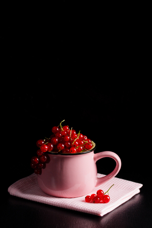 Redcurrant pile (ribes rubrum) in pink cup on pink napkin, dark wooden background. Cooking background, vertical orientation, place for copy space.