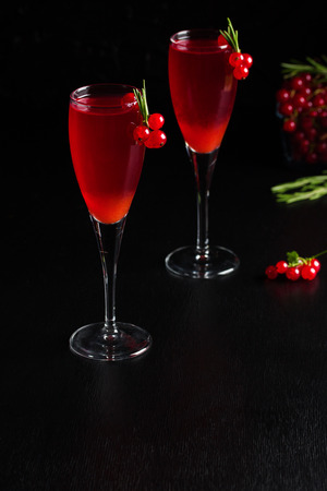 Two glasses of redcurrant wine drink juice decorated with rosemary and berries, a cup of redcurrant berries on dark wooden background. Vertical orientation, place for copyspace.