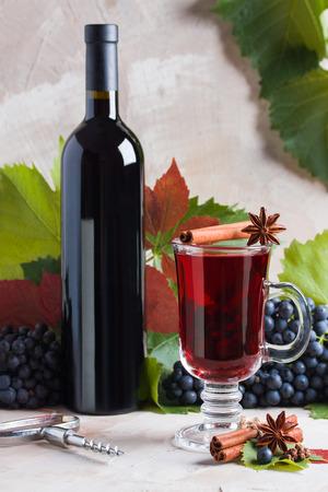 あなたのロゴタイプのための赤い熟したワインモックアップのボトルとグラス。赤ブドウ、スパイスシナモン、アニス、クローブ、緑と赤の葉、ベージュの背景にコルクスクリュー。赤のコンセプト新収穫ブドウ、秋の時間。 写真素材 - 106927622