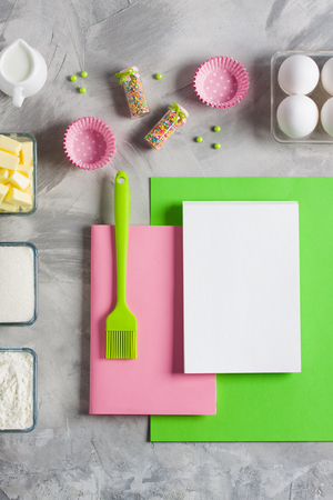 Cooking baking for kids flat lay background concept. Green paper pink notebook white pad kitchen tools silicone brush spatula, eggs, cups of sugar, flour, butter, cupcake molds jug of milk concrete.