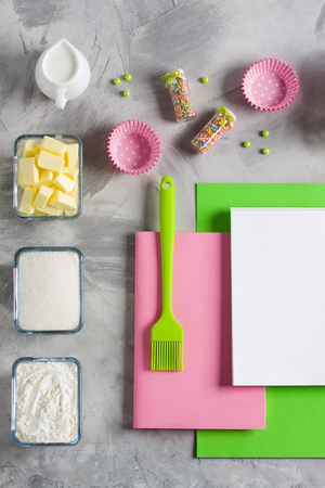 Cooking baking for kids flat lay background concept. Green paper pink notebook white pad kitchen tools silicone brush spatula, eggs, cups of sugar, flour, butter, cupcake molds, jug of milk, concrete.