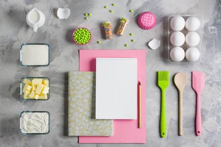 Cooking baking for kids flat lay background concept. Pink green paper white notebook kitchen    tools silicone brush spatula colored sprinkling eggs sugar flour butter cupcake molds milk jug    concrete.