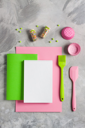 Green paper pink notebook white copy space for text or recipe, pen, colored sprinkling, cupcake molds, kitchen tools silicone brush, spatula. Concept cooking baking for kids, flat lay background.
