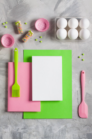 Cooking baking for kids flat lay background concept. Green paper pink notebook white pad kitchen tools silicone brush spatula, eggs, cupcake molds, jug of milk, colored sprinkling, concrete. Stok Fotoğraf