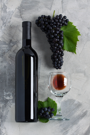 Bottle and glass of red wine, grapes with leaves on grey concrete background. Concept wine brand or sommelier. Vertical orientation, top view, flat lay.