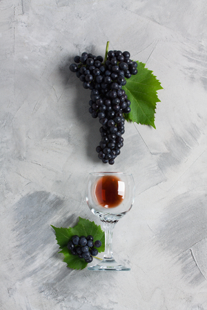 Glass of red wine, grape with leaves on grey concrete background. Concept wine from grapes,    brand or sommelier ads. Vertical orientation, top view, flat lay.