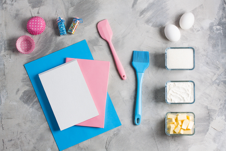 Cooking baking for kids flat lay background concept. Blue paper pink notebook white pad kitchen tools silicone brush spatula whisk eggs cups of sugar, flour, butter, cupcake molds concrete background.