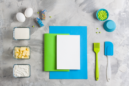 Cooking baking for kids flat lay background concept. Blue paper green notebook white pad kitchen tools silicone brush spatula eggs cups of sugar, flour, butter, cupcake molds concrete background. Stok Fotoğraf