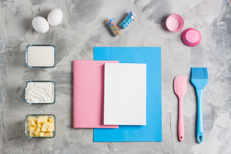 Cooking baking for kids flat lay background concept. Blue paper pink notebook white pad kitchen    tools silicone brush spatula whisk eggs cups of sugar, flour, butter, cupcake molds concrete    background. Stok Fotoğraf