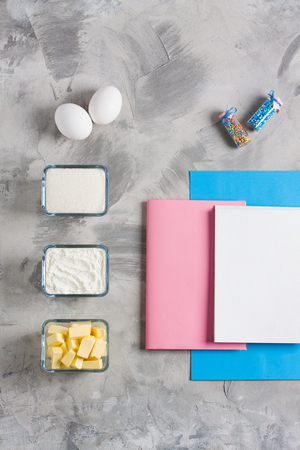 Cooking baking flat lay background with eggs, butter, flour, sugar, colored sprinkling, blue    paper pink notebook for recipe. Concept cooking baking for kids. Top view, flat lay, copy    space. Stok Fotoğraf