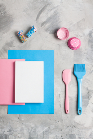 Cooking baking for kids flat lay background concept. Blue paper pink notebook white pad kitchen    tools silicone brush spatula, brush, cupcake molds, colored sprinkling on gray concrete    background. Stok Fotoğraf