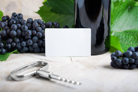White empty business card . Glass of wine, grape, green leaves on beige background.