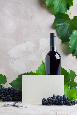 Bottle of red wine card mockup  , white paper card for text.  Concept new harvest of red grapes, autumn time.