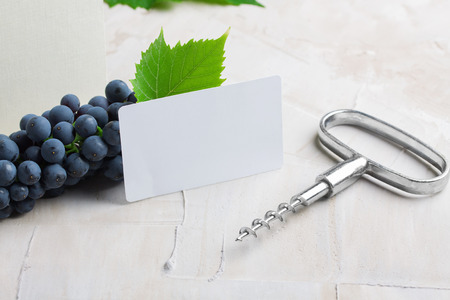 White empty business card . Glass of wine, grape, green leaves on it.   beige background. Concept wine brand, sommelier business card mockup.