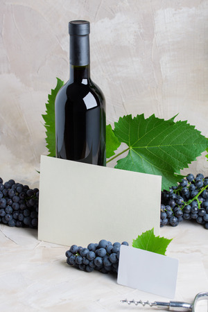 Bottle of red mulled wine mockup  , white paper card for text. Red grapes, green leaves, corkscrew on beige background. Concept new harvest of red grapes, autumn time. Stok Fotoğraf