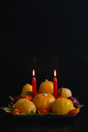 Halloween, thanksgiving, autumn still life composition with pumpkins, apples, dry leaves,  physalis, red candles on dark background.