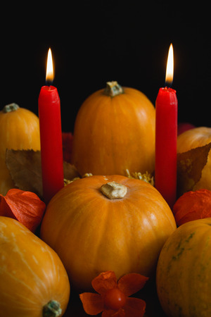 Halloween thanksgiving autumn still life composition with pumpkins apples dry leaves physalis red burning candles on dark background. Stok Fotoğraf