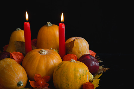 Halloween, thanksgiving, autumn still life composition with pumpkins, apples, dry leaves,  physalis, red candles on dark background. Table decoration concept, horizontal orientation.
