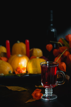 Glass of wine tea juice red drink dry leaves physalis. Halloween, thanksgiving, autumn still  life composition background, vertical orientation, close up.