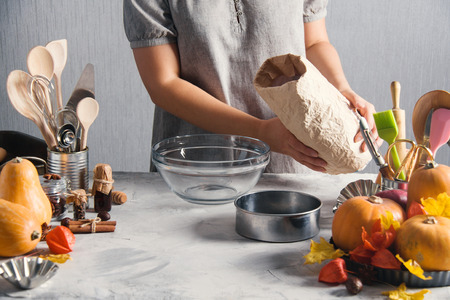 Woman cooking baking pack of flour pumpkins autumn time. Glass plate, sieve, pack of flour,    physalis, kitchen tools, spices, leaves, gray background. Stok Fotoğraf