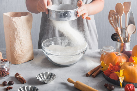 Woman sifts flour using sieve into glass bowl. Cooking, baking, pack of flour, pumpkins autumn    time, kitchen tools, wooden rolling pin, spices, cinnamon, nutmeg, gray background. Stok Fotoğraf