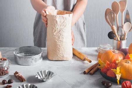 Woman holds pack of flour, wooden rolling pin sieve cooking baking. Pumpkins, autumn time,  kitchen tools, spices, cinnamon, nutmeg, anise.