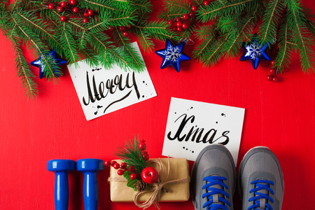 Christmas sport flat lay composition blue dumbbells sneakers gift box spruce tree branches Merry Christmas lettering red wooden background. Concept Christmas special for healthy lifestyle and sport.