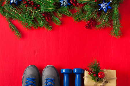 Christmas sport flat lay composition with blue dumbbells sneakers gift box and spruce tree branches red wooden background. Concept Christmas special for healthy lifestyle and sport. Stok Fotoğraf