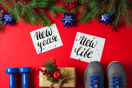 Christmas sport flat lay composition blue dumbbells sneakers gift box spruce tree branches new    year new life lettering red wooden background. Concept new year special for healthy lifestyle and    sport. Stok Fotoğraf
