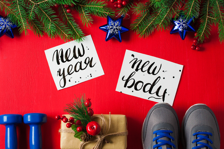 Christmas sport flat lay composition blue dumbbells sneakers gift box spruce tree branches new    year new body lettering red wooden background. Concept new year special for healthy lifestyle and    sport.