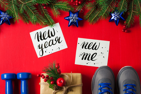 Christmas sport flat lay composition blue dumbbells sneakers gift box spruce tree branches new    year new me lettering red wooden background. Concept new year special for healthy lifestyle and    sport. Stok Fotoğraf