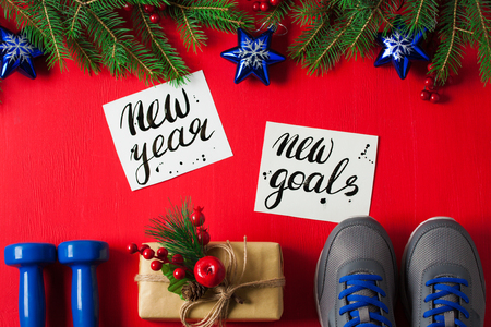 Christmas sport flat lay composition blue dumbbells sneakers gift box spruce tree branches new    year new goals lettering red wooden background. Concept new year special for healthy lifestyle    and sport. Stok Fotoğraf