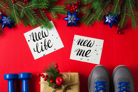 Christmas sport flat lay composition blue dumbbells sneakers gift box spruce tree branches new    life new me lettering red wooden background. Concept new year special for healthy lifestyle and    sport. Stok Fotoğraf