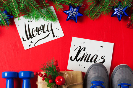Christmas sport flat lay composition blue dumbbells sneakers gift box spruce tree branches Merry    Christmas lettering red wooden background. Concept Christmas special for healthy lifestyle and    sport. Stok Fotoğraf