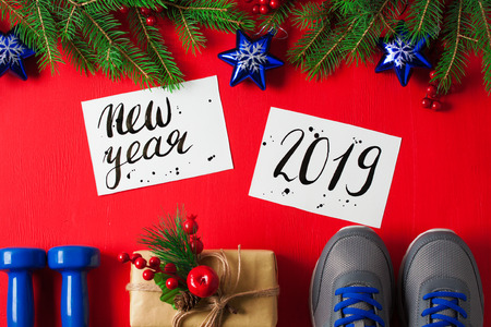 Christmas sport flat lay composition blue dumbbells sneakers gift box spruce tree branches new    year 2019 lettering red wooden background. Concept new year special for healthy lifestyle and    sport.