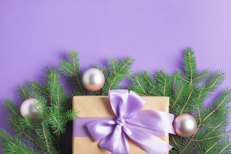 Christmas composition with spruce tree branches, craft gift box with lilac bow, pink balls on purple background. Top view, horizontal orientation, place for copy space.