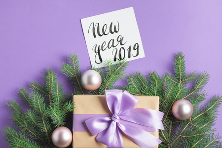 Christmas composition with spruce tree branches, craft gift box with lilac bow, pink balls, new year 2019 lettering on purple background. Top view, horizontal orientation, place for copy space.