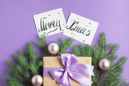 Christmas composition with spruce tree branches, craft gift box with lilac bow, pink balls, Merry Christmas lettering on purple background. Top view, horizontal orientation, place for copy space. Stok Fotoğraf
