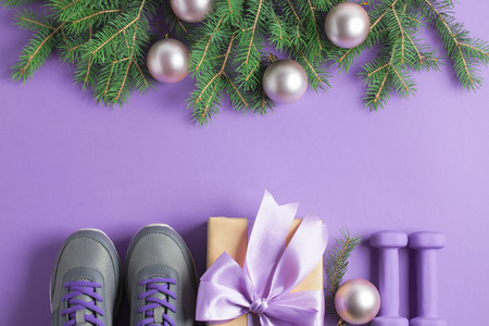 Christmas sport flat lay composition gray shoes, purple dumbbells, craft gift box with lilac bow, spruce tree branches on violet background. Top view, horizontal orientation.