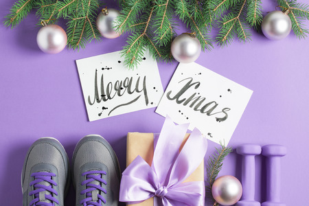 Christmas sport flat lay composition gray shoes, purple dumbbells, craft gift box with lilac bow, spruce tree branches, Merry Christmas lettering on violet background. Top view, horizontal. Stok Fotoğraf