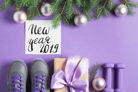 Christmas sport flat lay composition gray shoes, purple dumbbells, craft gift box with lilac bow, spruce tree branches, new year 2019 lettering on violet background. Top view, horizontal. Stok Fotoğraf