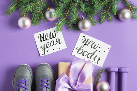 Christmas sport flat lay composition gray shoes, purple dumbbells, craft gift box with lilac bow, spruce tree branches, lettering on violet background. New year new body concept. Top view horizontal.