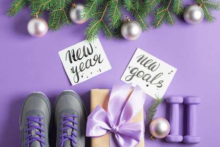 Christmas sport flat lay composition gray shoes purple dumbbells craft gift box with lilac bow spruce tree branches lettering on violet background. New year new goals concept. Top view horizontal.