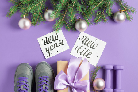 Christmas sport flat lay composition gray shoes purple dumbbells craft gift box with lilac bow spruce tree branches lettering on violet background. New year new life concept. Top view horizontal. Stok Fotoğraf
