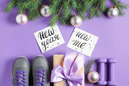 Christmas sport flat lay composition gray shoes purple dumbbells craft gift box with lilac bow spruce tree branches lettering on violet background. New year new me concept. Top view horizontal. Stok Fotoğraf