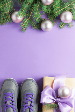 Christmas sport flat lay composition gray shoes, purple craft gift box with lilac bow, spruce tree branches on violet background. Top view, vertical orientation.