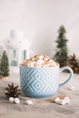 Christmas and Happy New Year cozy composition blue mug white pattern of cacao marshmallows, cones, candle lamp and fir-trees, gray concrete background. Xmas greeting card, winter holiday concept.